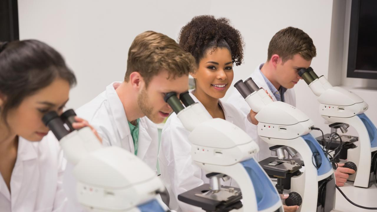 Medical students researching using lab equipment