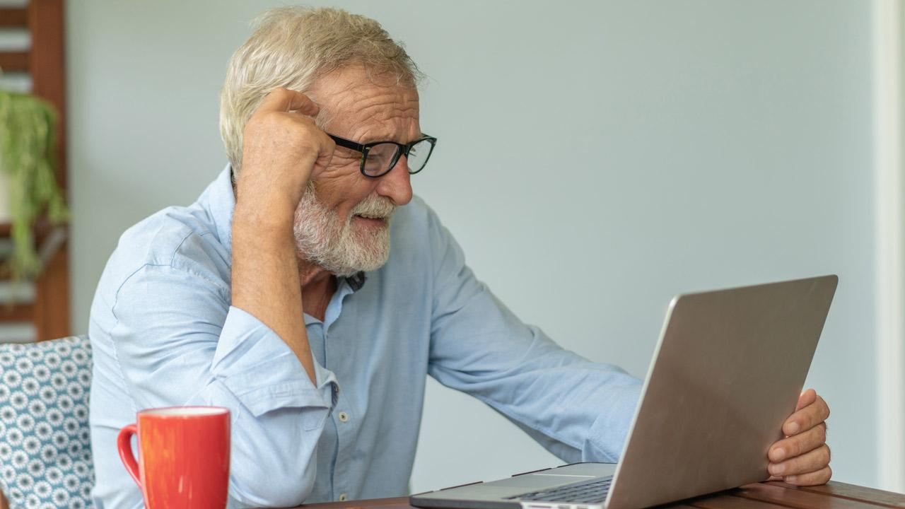 An older man taking a course remotely.