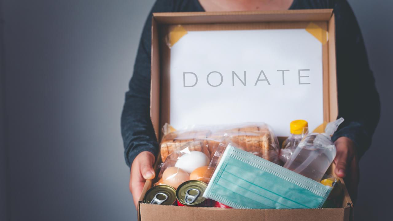 A person holding a box full of donations that says donate.