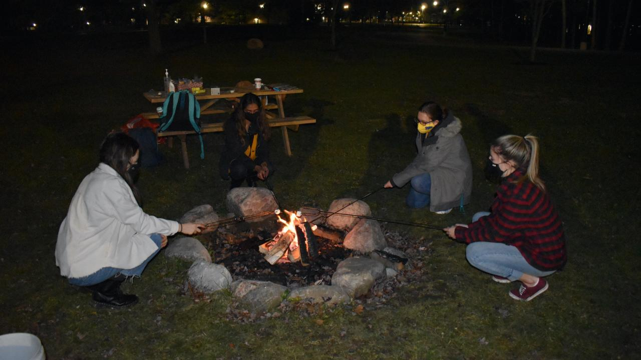 Students sitting around a campfire.