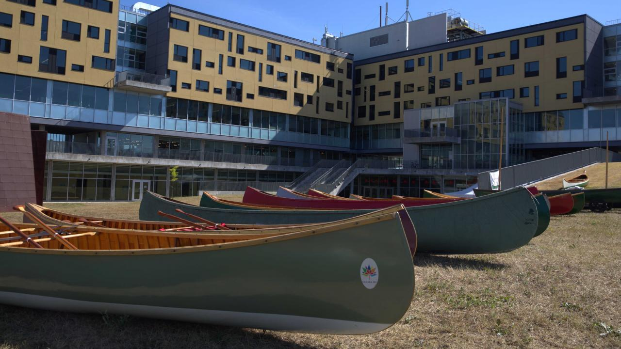 Canoes lined up in front of Peter Gzkowski College