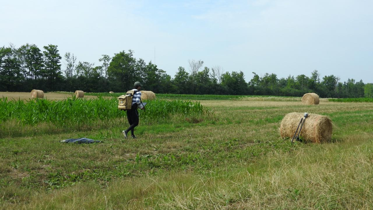 A student using technology in a field.