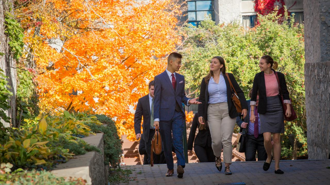 A group of business students walking together on campus.
