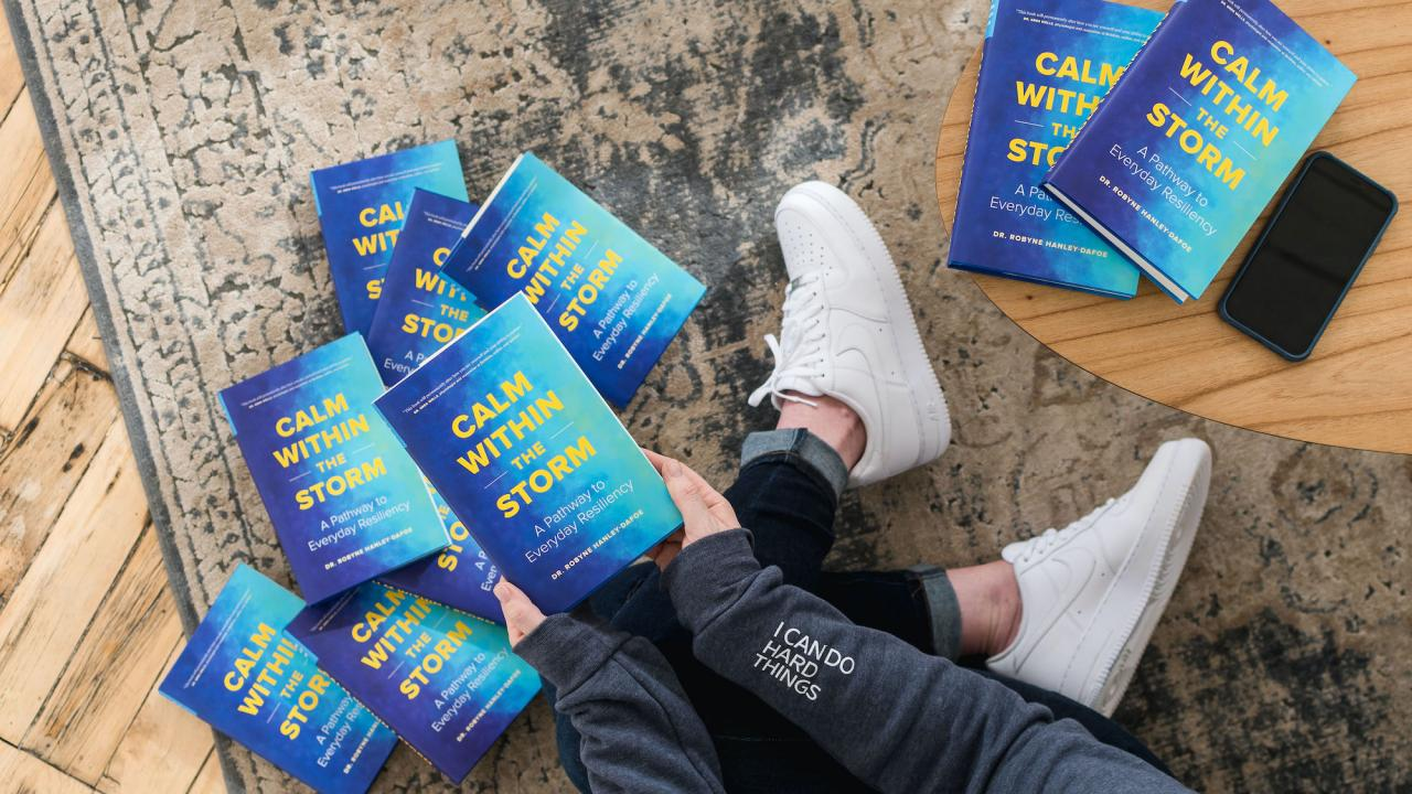 """A person's legs surrounded by copies of """"Calm Within the Storm"""" by Dr. Robyne Hanley-Dafoe scattered on the floor."""