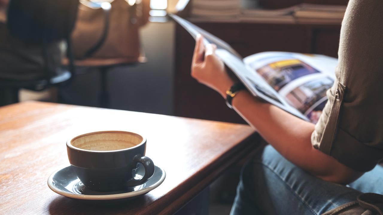 A person reading a magazine with a cup of coffee on a table beside them.