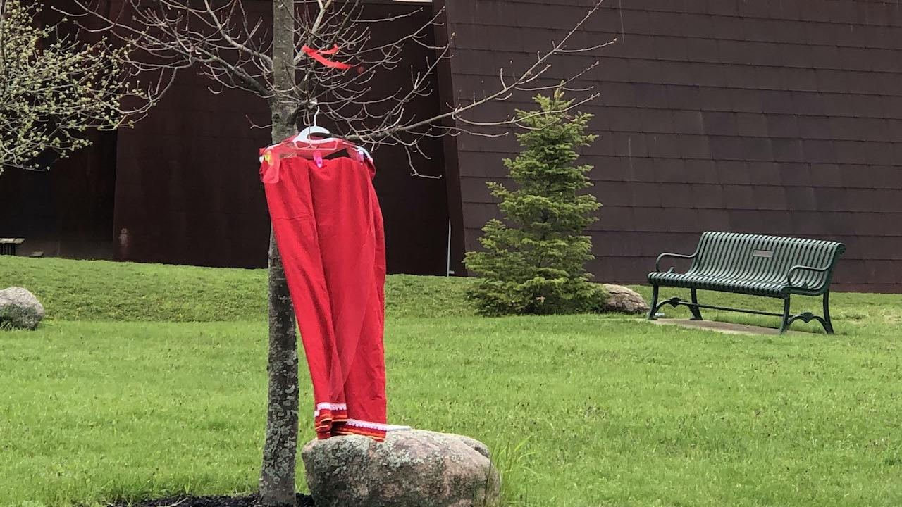 A red dress hangs on a tree outside of Trent University's Enwayaang building