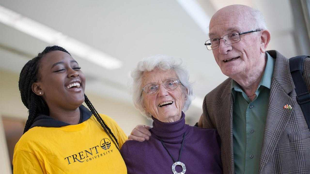 A Trent student volunteer laughing with two senior citizens.