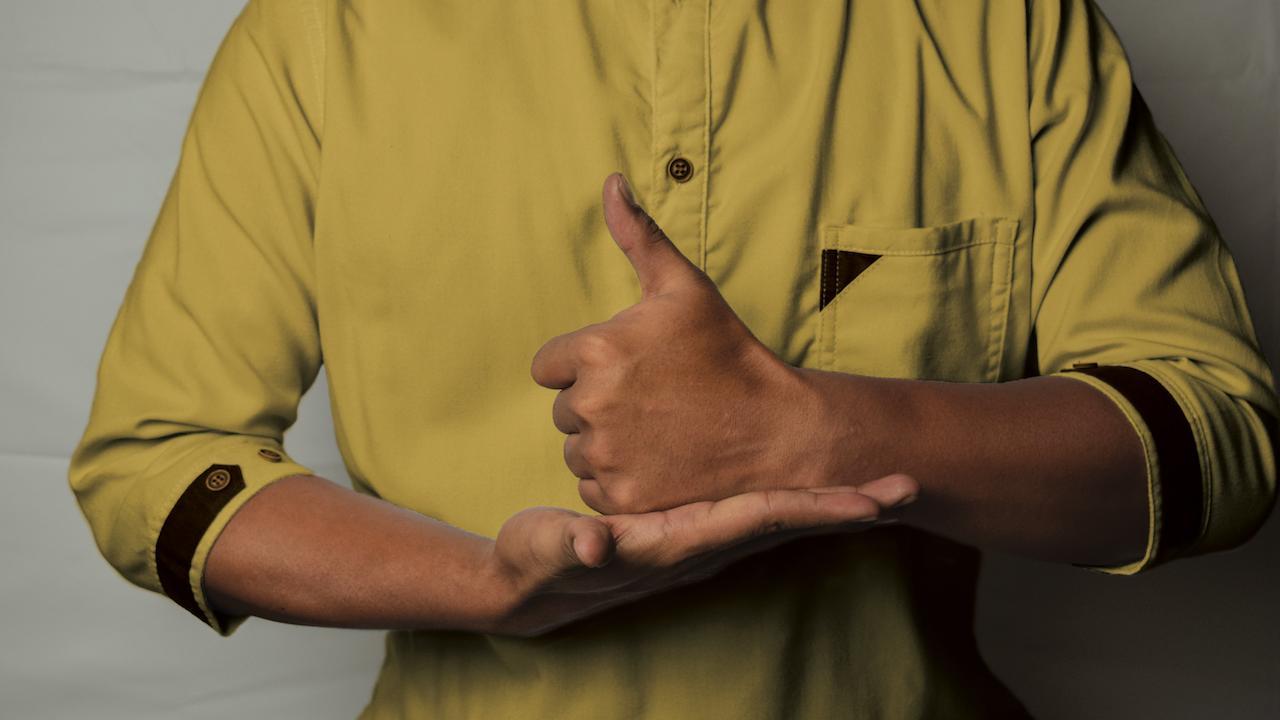 A man using American Sign Language to communicate.