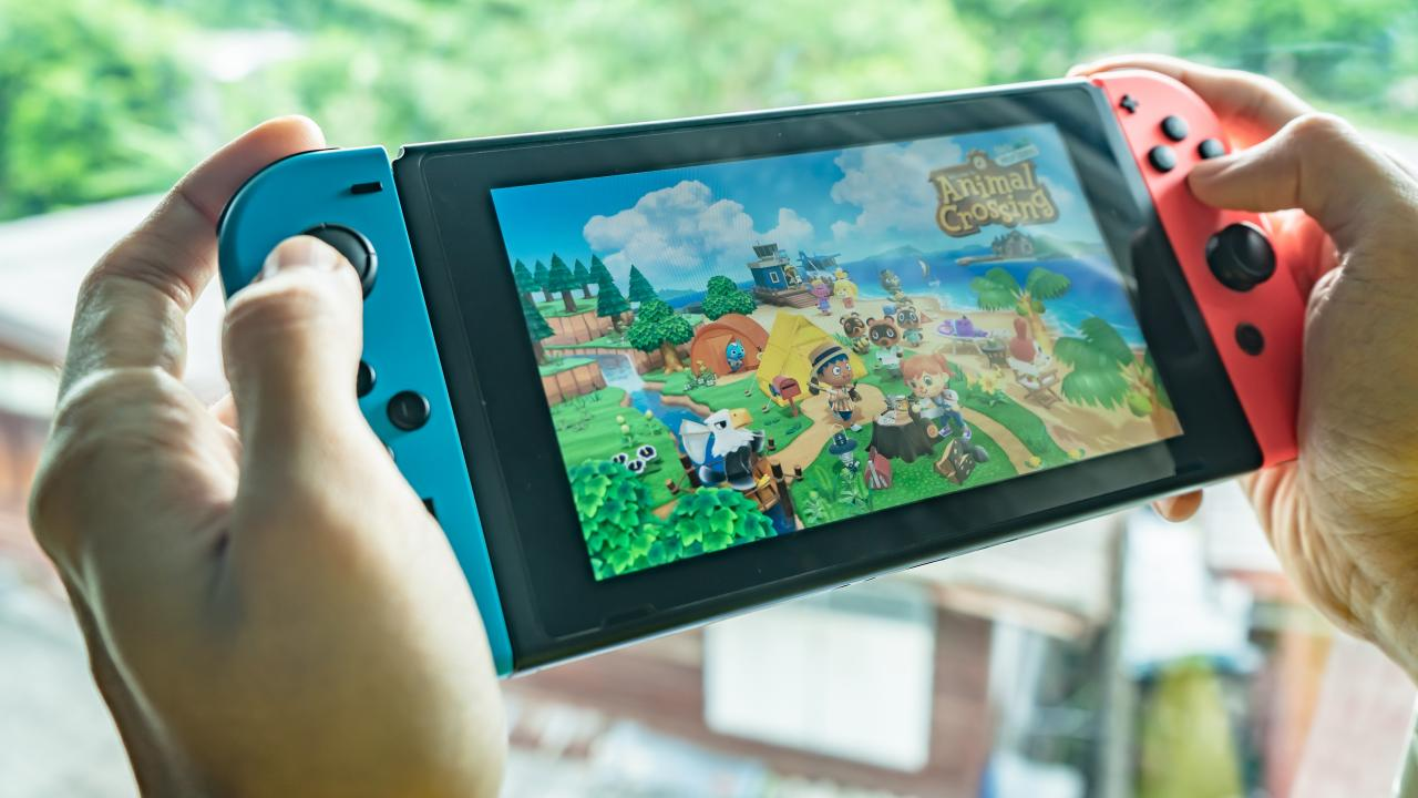 Close up of an individual holding a Nintendo Switch with thumbs on the controls with the game Animal Crossing displaying on the screen