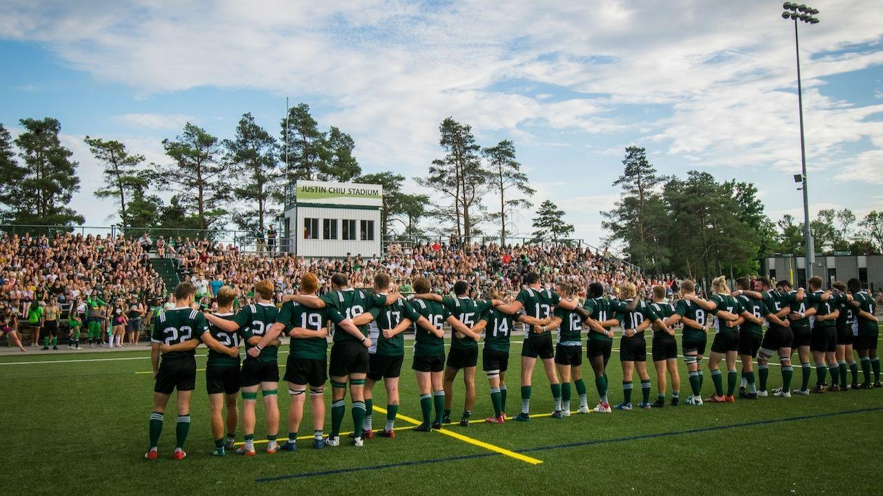 The Trent Men's Varsity Rugby Team standing together in front of a crowd at Justin Chiu Stadium.