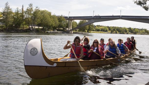 A group of people sitting in a canoe paddlig down the Otonabee river with the Faryon bridge in the background