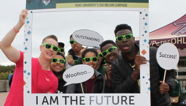 """A group of young adults smiling at the camera and holding up a window frame that reads """"I am the Future"""""""