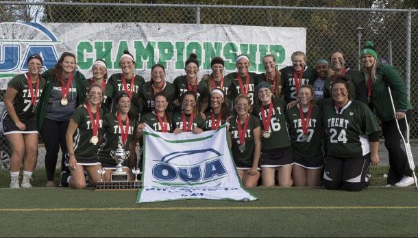 Lacrosse team standing in front of a banner reading OUA Championship
