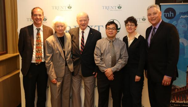 The dean of Arts & Sciences, Holger Hintelmann, along with Dr. Fei Wang and 4 other individuals standing together in front of a Trent University poster at the lecture at Market Hall.