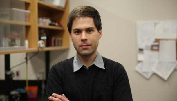 Dr. Robert Huber standing in a lab room in a black sweater with his arms crossed and a faint smile.