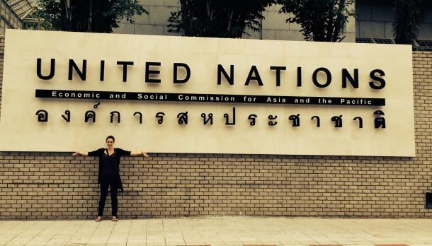 Landscape photo of Jennifer Boyce standing in front of sign for United Nations Economic and Social Commission for Asia and the Pacific