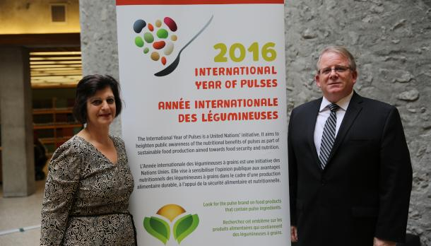 "A man and woman standing next to each other in front of a sign in bata library that says ""2016, International Year of Pulses"""