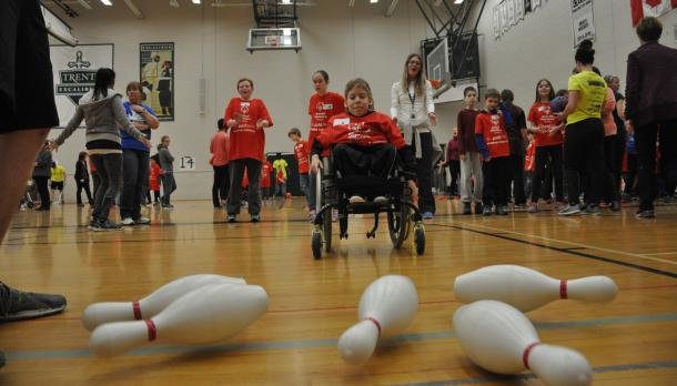 Trent University Excalibur athletes and Special Olympics participants in the gymnasium in front of five bowling pins knocked over