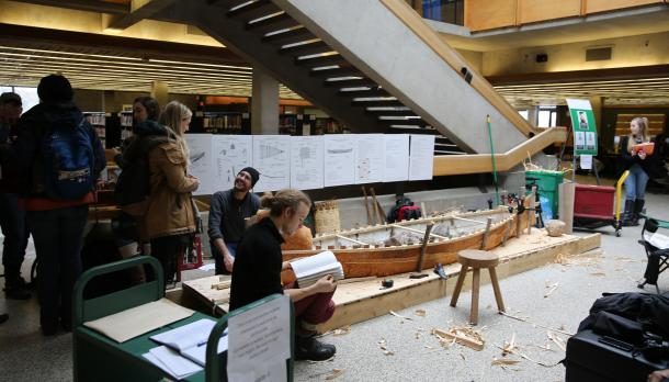 The canoe partially built in Bata, with people around it talking and looking at books.