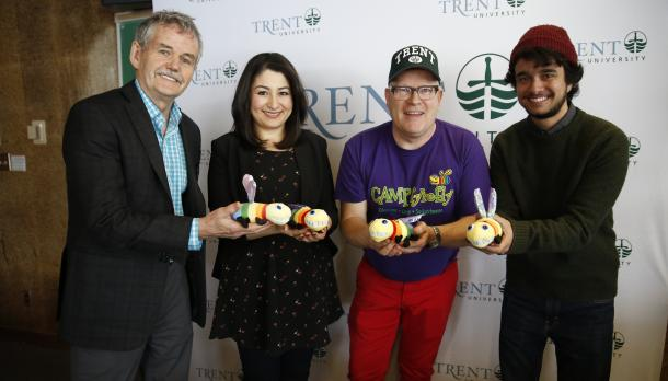 Leo Groarke, Mariam Monsef, Spencer J. Harrison, and Jasper standing in front of  Trent University banner, smiling and each holding a stuffed firefly in rainbow colours.