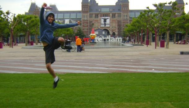 fellow student jumping out of excitement in front an old building with Amsterdam sign while wearing a blue hoodie