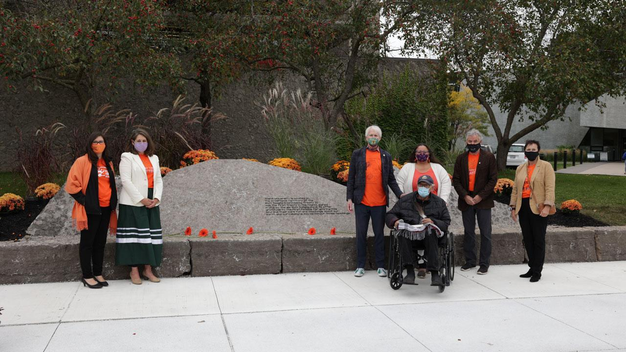 New treaty rock installation on Trent's Peterborough campus was unveiled. Photo includes (L-R) Curve Lake First Nation Chief Emily Whetung; Julie Davis, VP of External Relations and Advancement; Chancellor Stephen Stohn; Elders Doug Williams and Anne Taylor of Curve Lake First Nation, Trent President Leo Groarke; and Debra Cooper Burger, chair of Trent University's Board of Governors.