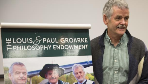 Leo Groarke smiling and standing in front of a poster with his brothers on it