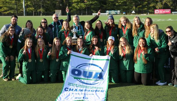 Trent women's lacrosse team and Trent President Leo pose with Gold medals after winning championship