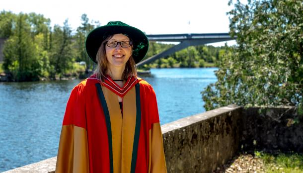 trent Ph.D graduate stands beside the faryon bridge at trent university during graduation