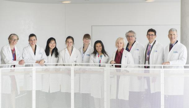 group of doctors stand in a line smiling after Trent university student completes medical research