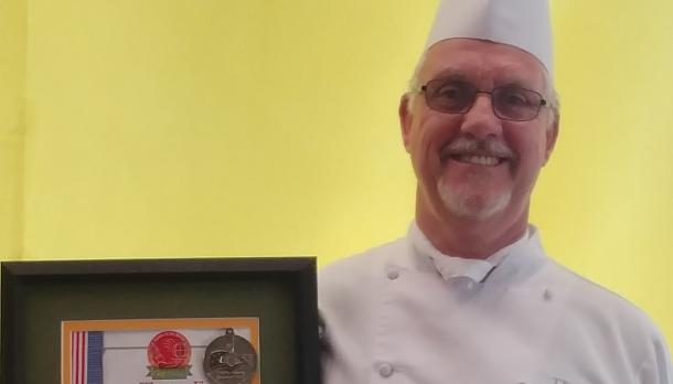 chef wins award and poses infront of yellow wall at Trent university
