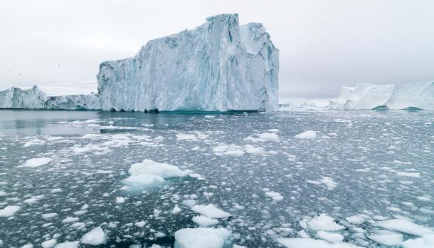 A large glacier in the ocean with broken ice all around it