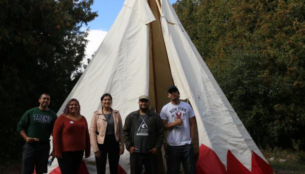 5 trent university students and faculties standing in front of the new Tipi