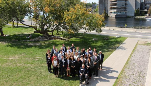 A group of people standing together at Trent University with the Otonabee River and Bata Library in the background