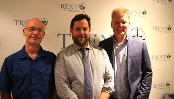 3 men standing together and smiling in front of a Trent University sign