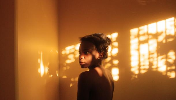 A girl standing in a dimly lit room with her bare back exposed