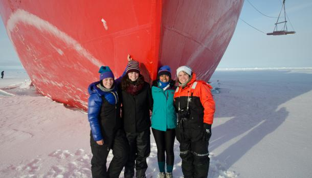 Trent master student at arctic standing in front of the Canadian ship on the ice with couple of other researcher