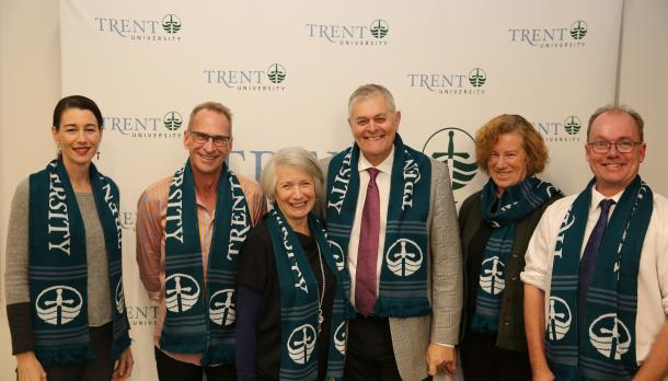 Trent University Faculties and staff standing in front of Trent University Back Drop smiling to camera