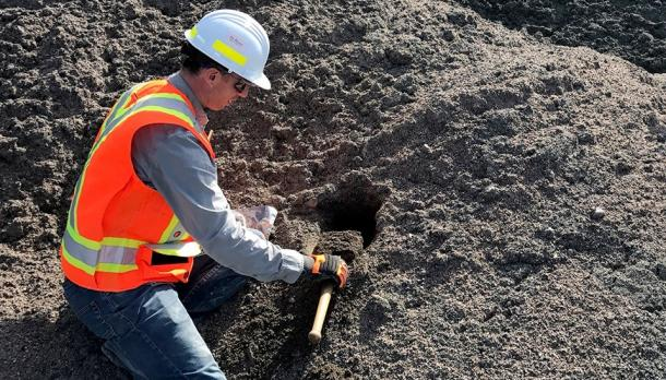 Man with hard hat and vest on digging in the dirt
