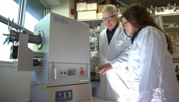 Man and woman with white coats on in a lab looking at a machine