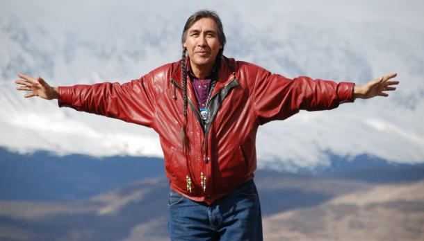 Man with long dark hair wearing red leather jacket with arms spread in front of mountain landscape