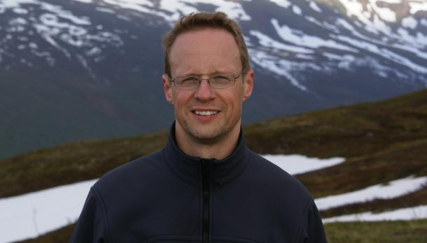 Man with light brown hair and glasses standing in front of mountains