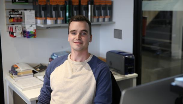 Alex Salton sitting in an office smiling at camera