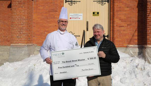 Christopher Ennew holding large cheque with male representative from Brock Street Mission