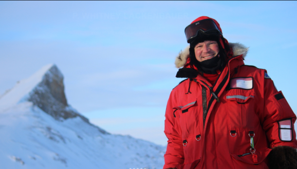 Dr. Whitney Lackenbauer in a big red winter jacket in front of a mountain peak