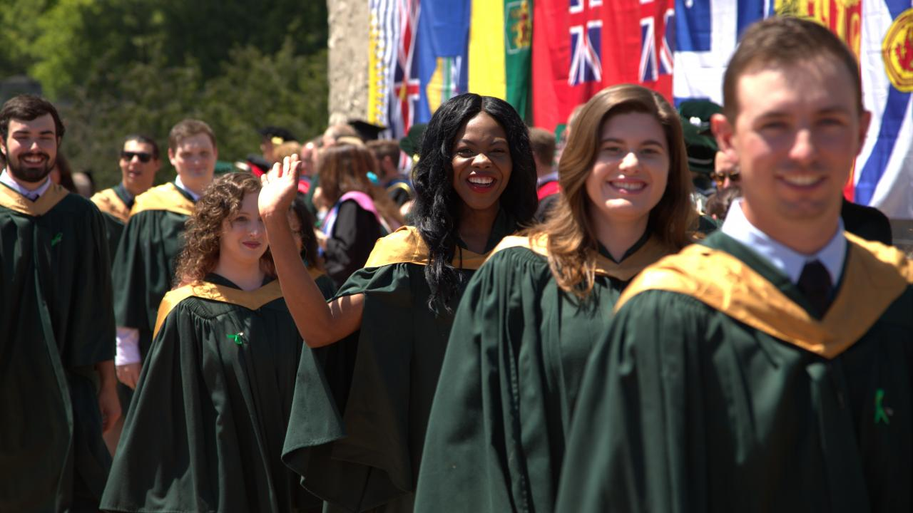 Trent University students walking during Convocation procession in gowns