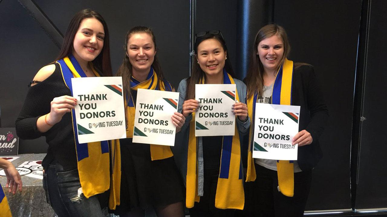 """Four Trent Alumni hold up signs with the words """"Thank you donors"""" printed on them."""
