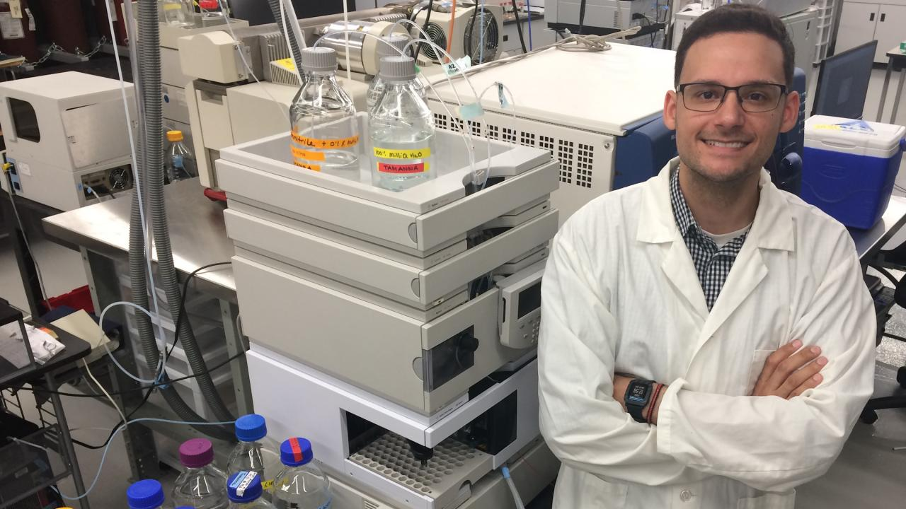 Researcher in white lab coat at a lab, crossing his arms and standing next to lab equipment