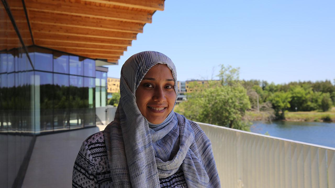 Bayan Sajer waring scarf and sweater on the balcony of the Student Centre on a sunny day.