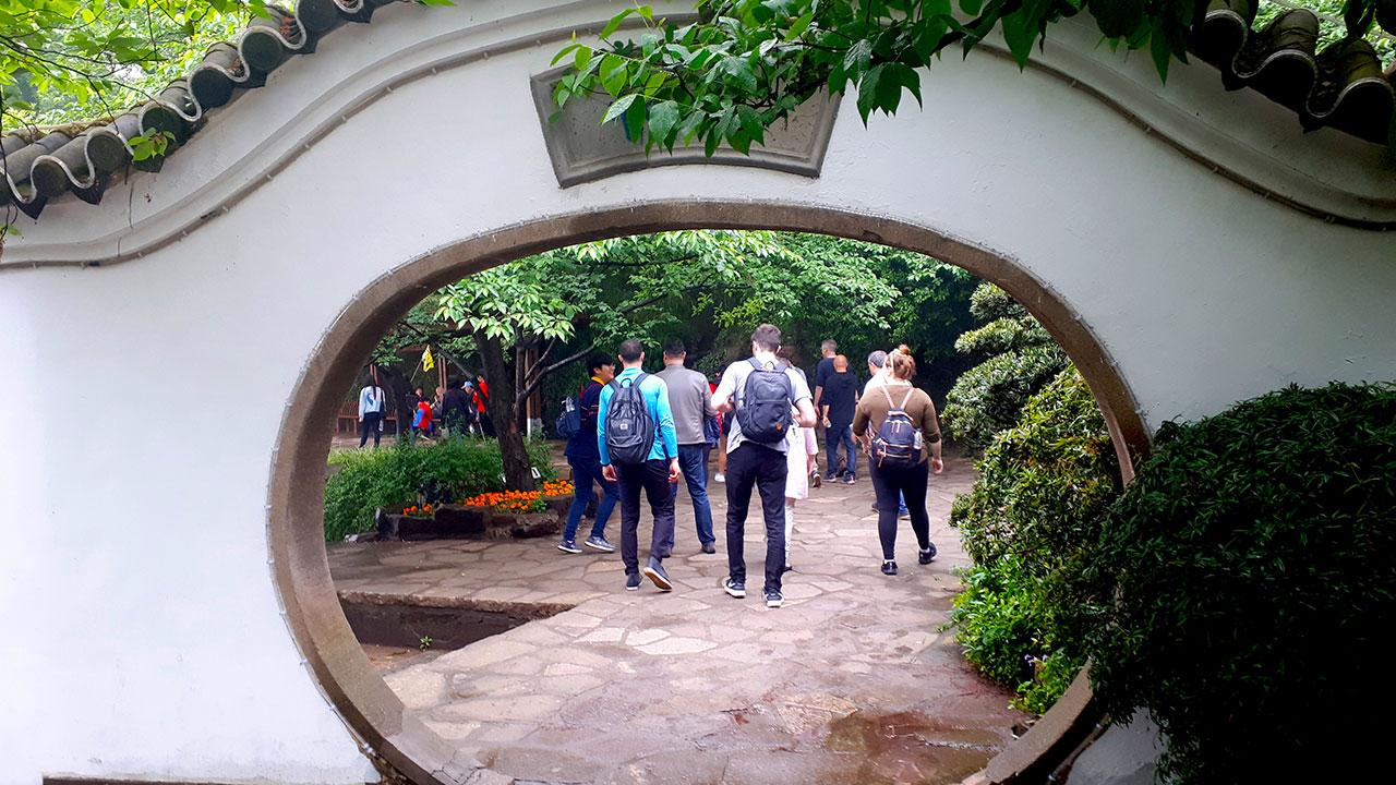 People walking along a stone pathway in a public garden in China.